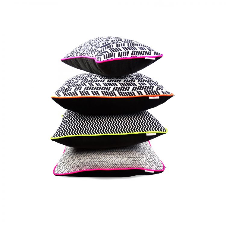 Group of geometric print cushions with neon piping and velvet back