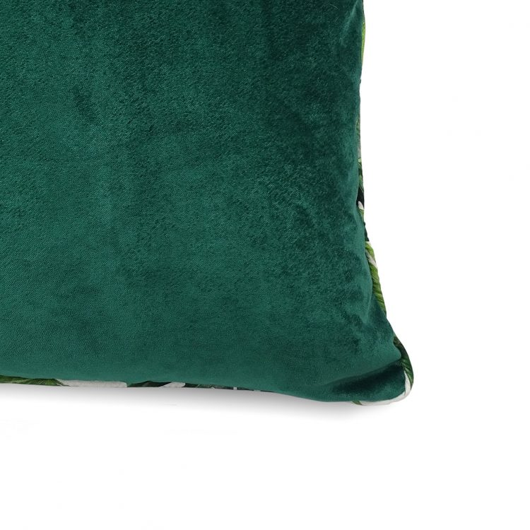 Close up of green velvet cushion cover with tropical leaf piping